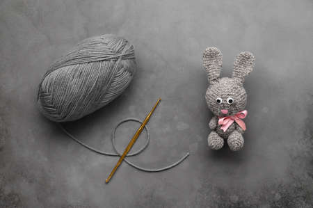 Easter crafting DIY. Handmade crochet rabbit toy, ball of wool yarn, and knitting needle on dark gray background.