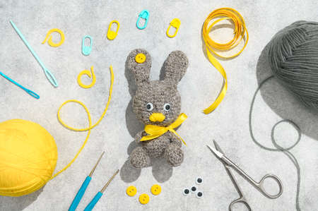 Easter crafting DIY. Handmade knitted toy Easter rabbit, and needlework accessories on gray background. Overhead view, flat lay