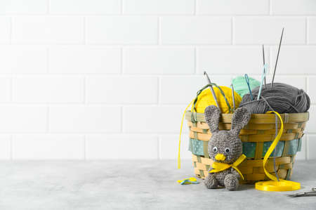 Easter crafting DIY. Handmade knitted toy Easter rabbit, and knitting accessories in the basket. White brick backdrop. Space for text 版權商用圖片