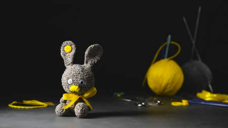 DIY Easter gift making theme. Handmade knitted toy Easter rabbit and needlework accessories. Black backdrop. Knitting concept. Dark moody style