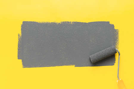 Colors of the year 2021 Ultimate Gray and Illuminating Yellow. Paint roller painting a gray stripe on a yellow background. Minimalistic composition with copy space