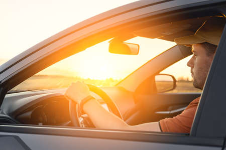 Caucasian Man in automobile in the countryside and sun rays. Male driver driving a car at sunset background. Summer travel, road trip and vacations concept