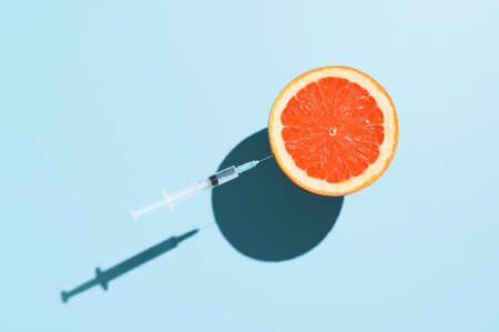 vaccination creative concept. Half grapefruit and a syringe with a vaccine  , levitating over pastel blue background. Minimalistic image, top view Banco de Imagens
