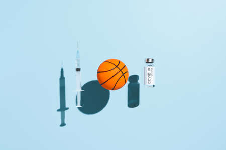 vaccination concept. Vial vaccine, medical syringe, and basketball ball in form virus, levitating over pastel blue background. Top view Banco de Imagens