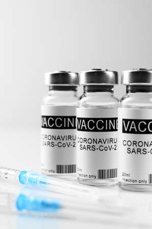 Coronavirus vaccination theme. Three vials with COVID-19 vaccine and syringes on glass laboratory white bench, close up Banco de Imagens
