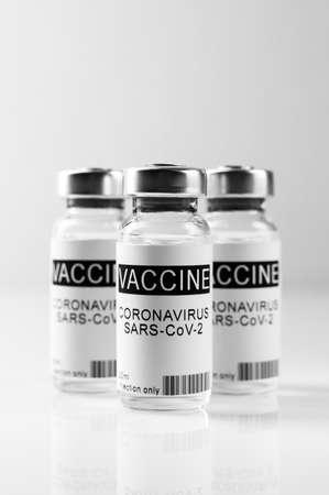 Coronavirus vaccination theme. Three glass vials with COVID-19 vaccine on white laboratory bench, close up