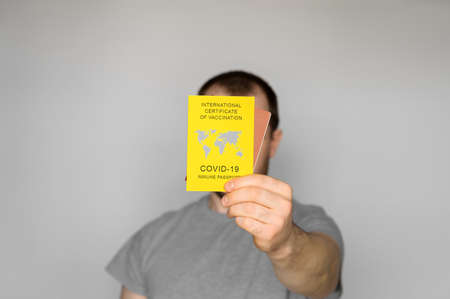Adult man wearing t-shirt holding yellow International Certificate of Vaccination on gray background. Traveling Immune passport, as proof vaccinated against Covid-19. Close-up