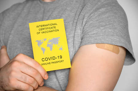 Adult man wearing gray t-shirt holding an International Certificate of Vaccination and shows his arm after vaccination. Traveling Immune passport, as proof vaccinated against Covid-19. Close-up