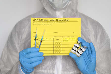 Medical worker wearing protective suit holding yellow Vaccination record card, syringes, and vials with COVID-19 vaccine for two-stage injection. Gray background, close up