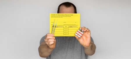 Adult man wearing t-shirt holding yellow Vaccination record card, syringes, and vials with COVID-19 vaccine for two-stage injection. Gray background Banco de Imagens