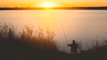 Silhouette fisherman sitting with a fishing rod on the shore of the lake during sunset. Hobby concept and mental health Banco de Imagens