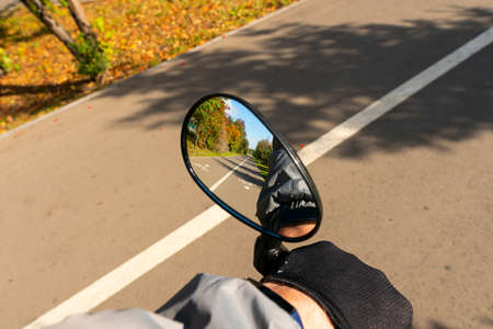 Beautiful sunny summer day. Reflection in the rearview mirror of two-way asphalt bike path in the urban park in perspective