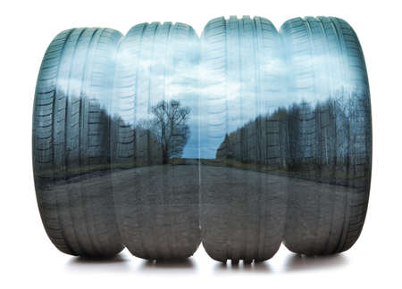 Double exposure of a car tire close-up and suburban asphalt road in the forest. Horizontal orientation.