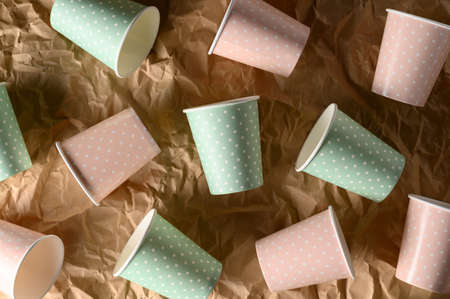 From above of arranged color paper cups on crumpled craft paper. Plastic-free concept, biodegradable tableware, recyclable. Zero waste