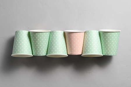 From above of arranged in row color paper cups on gray background. Plastic-free concept, biodegradable tableware, recyclable. Zero waste Banco de Imagens
