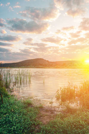 Bright summer sunrise over a lake with hills and clouds in the sky Banco de Imagens