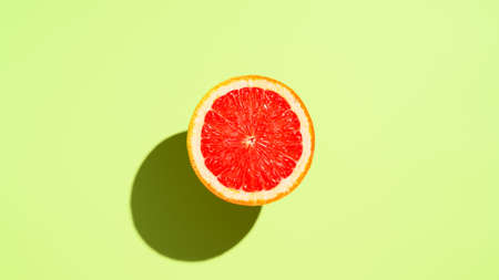 Grapefruit half on pastel green background. Top view, flat lay. Place for text