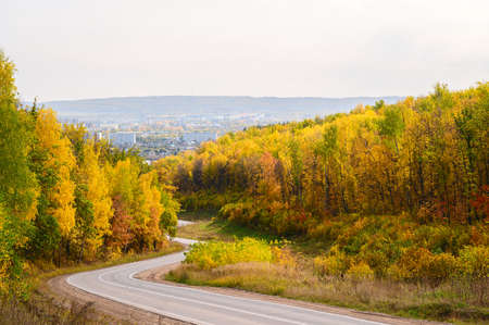 A winding asphalt road through a picturesque autumn forest leading to the city. Beautiful sunny autumn day.