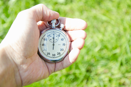 stop watch: Sports stop watch in a hand on a grass background Stock Photo