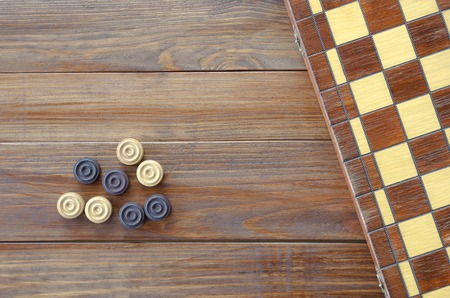 checkers: Checkers on a wooden background