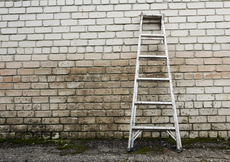raiser: Metal ladder staircase on brick wall background