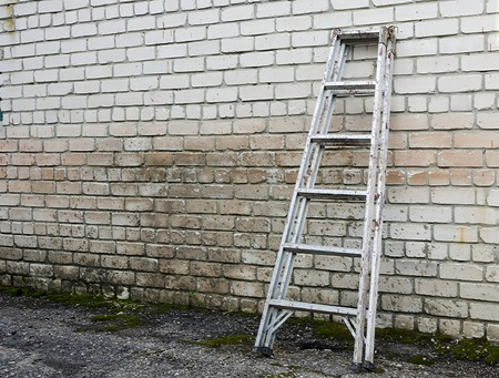 raiser: Old Ladder staircase against a brick background