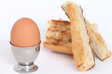 accompanied: close up of whole egg in an egg cup Accompanied by toast slices