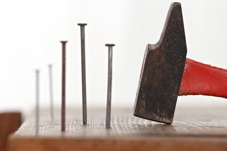 to tinker: close up of nails planted in a wooden cabinet with a hammer to tinker