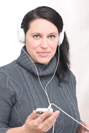 Femme heureuse écouter de la musique avec un casque et de porter des vêtements d'hiver et chapeau Banque d'images - 52520029