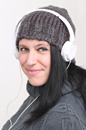 Femme heureuse écouter de la musique avec un casque et de porter des vêtements d'hiver et chapeau Banque d'images - 52520031
