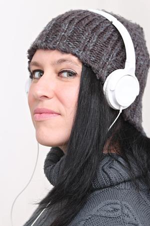 Femme heureuse, écouter de la musique avec des écouteurs et porter des vêtements d'hiver et un chapeau Banque d'images - 52520033