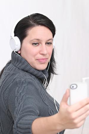 Femme heureuse écouter de la musique avec un casque et de porter des vêtements d'hiver et chapeau Banque d'images - 52520041