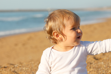 Happy blond baby playing at the beach Banque d'images - 87927079