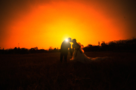 Couple kissing with sunset photo