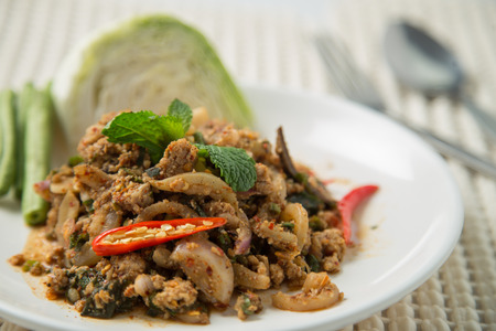Hot and spicy with fried pork mixed with basil leaf very famous of Thai food photo