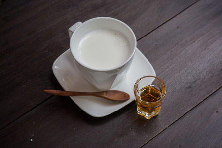 cup of milk with honey on wood table photo