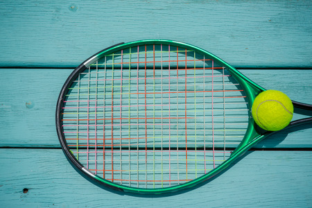 A tennis racket with tennis ball on green wood texture Banco de Imagens