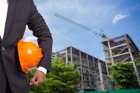 engineer holding orange helmet for workers security on contruction background Standard-Bild