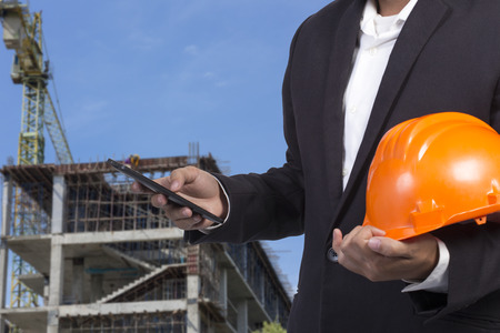 engineer holding orange helmet for workers security on contruction background Standard-Bild