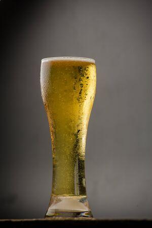 unbottled: Glass of light beer on black background