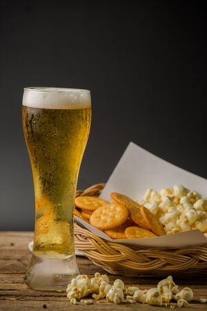 Beer Glass and Popcorn on a Wooden Background photo
