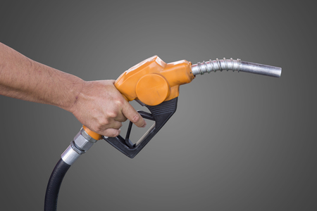 petroleum fuel: Holding a fuel nozzle against grey background Stock Photo