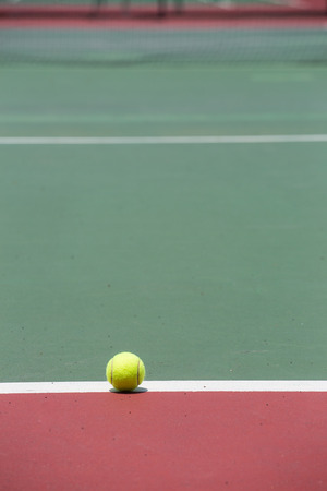 avocation: Tennis Ball on the Court with the Net in the background Stock Photo