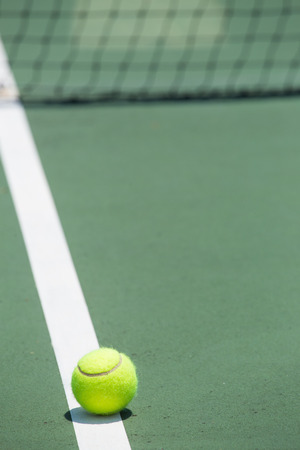 Tennis Ball on the Court with the Net in the background photo