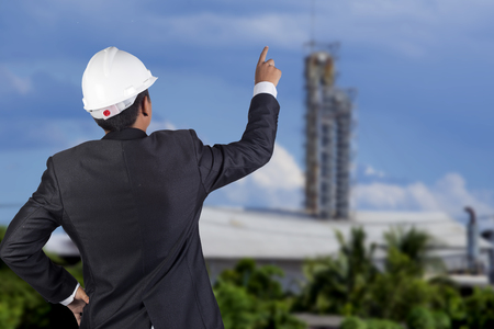 engineer in suit stand in front of construction site photo