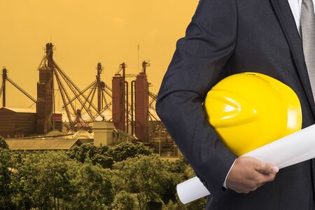 indenture: engineer hand holding yellow helmet for workers security and blueprint paper plan against the background of construction