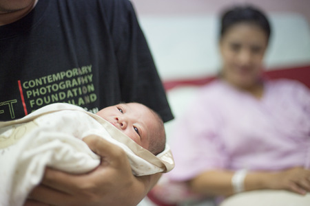 birthing: new born infant  in the blanket in hospital room