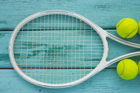 tennis racket with tennis ball on green wood texture Standard-Bild