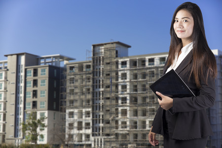 developing: building, developing, construction and architecture concept - smiling woman Stock Photo