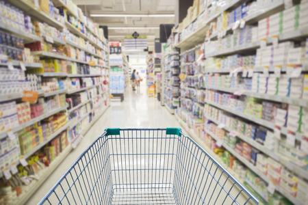 Supermarket interior, empty green shopping cart